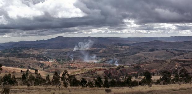 à l'horizon le massif Andringitra la fumée révèle la fabrication du charbon de bois